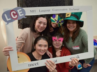 Five LCE members posing in for a photo wearing colorful masks and party hats